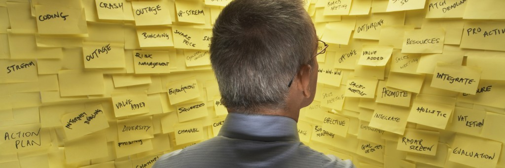 Middle-aged man standing in front of wall covered in sticky notes, reading, back view