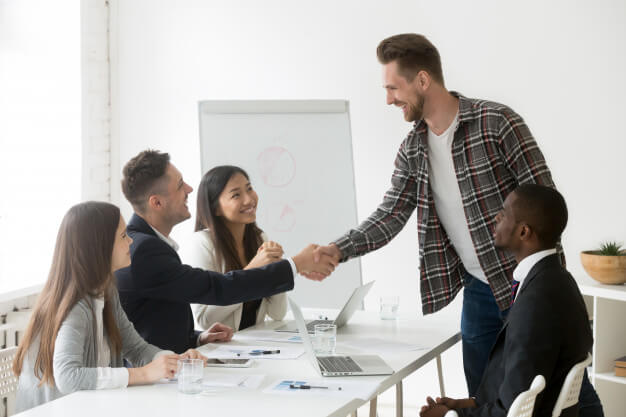 smiling-businessman-welcoming-new-partner-group-meeting-with-handshake_1163-4627